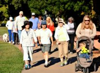 Group of people of all ages walking in a park