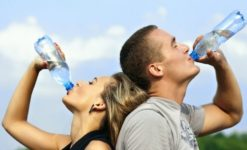 two people drinking from water bottles to stay hydrated