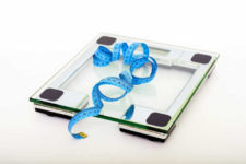 Scale with bright blue tape measure curled on top of it